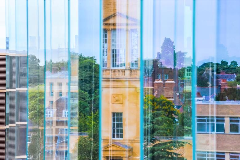 Image of the Radcliffe observatory taken from a window with a number of different reflections including buildings, tree